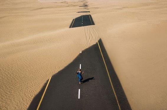 woman walking down sandy road