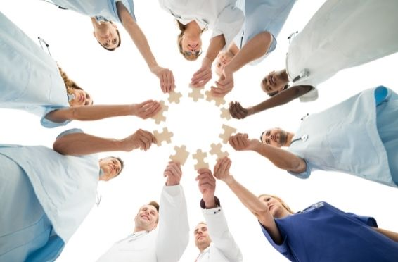 medical team holding puzzle pieces in a circle